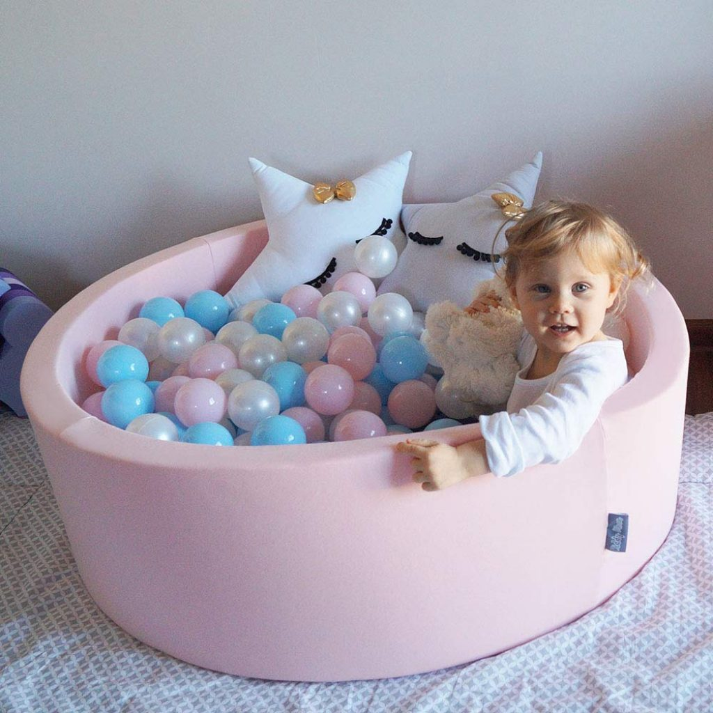 Cette petite fille joue dans sa piscine à balles en mousse rose.